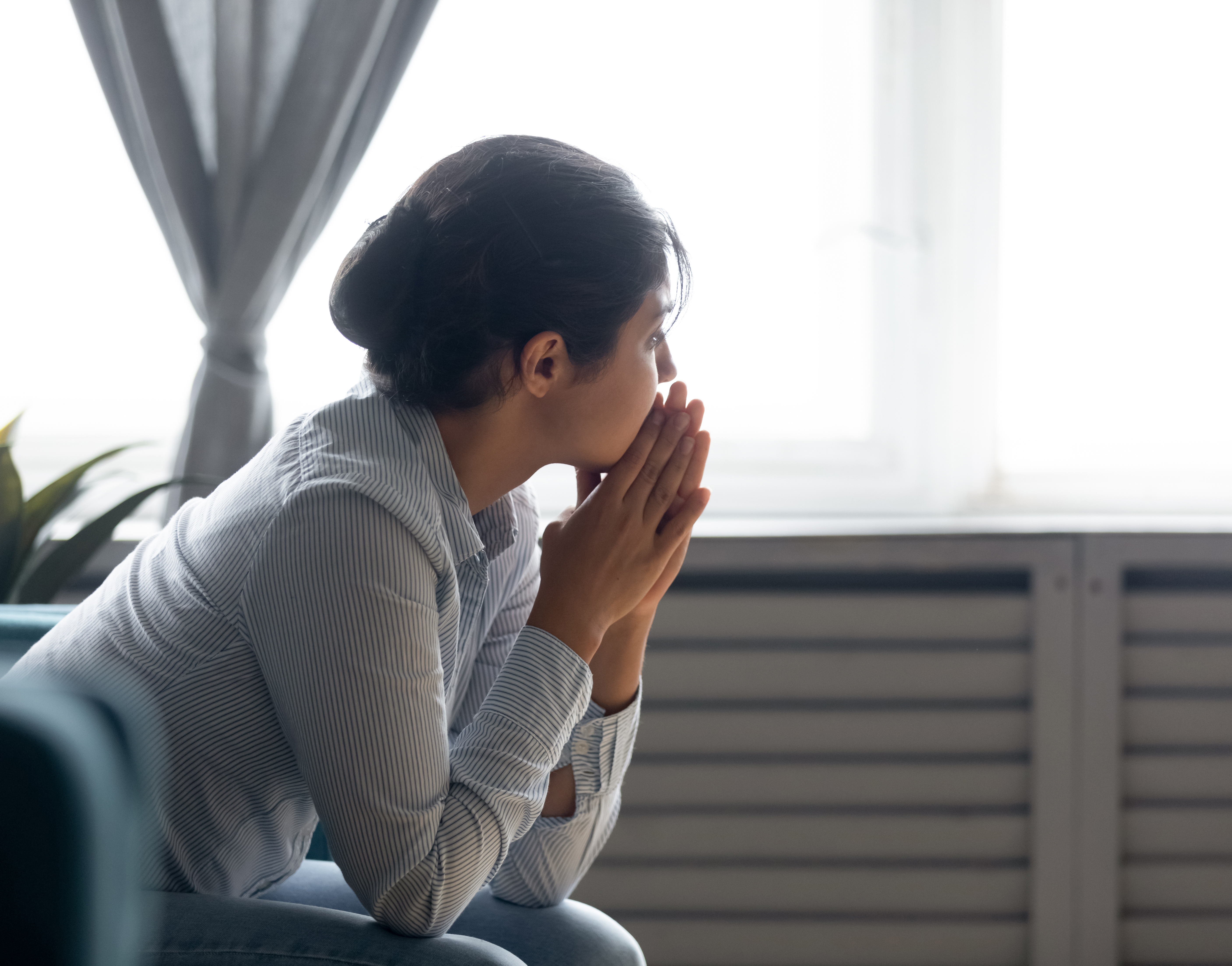 A person sitting and thinking by the window